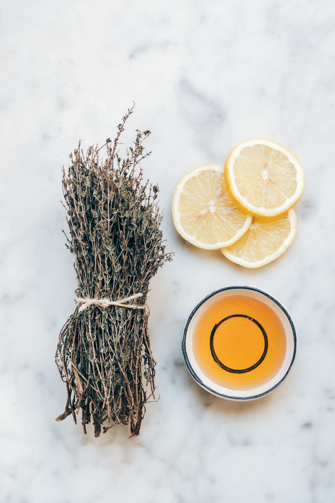 A bundle of thyme next to lemon slices and a small bowl of honey