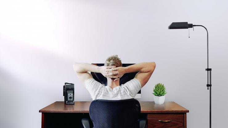 Guy sitting at desk with hands on his head
