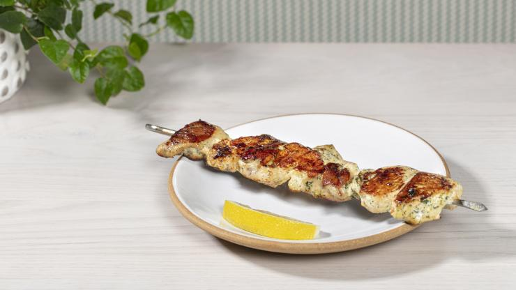 Chicken kebab with summer savory marinade on a plate with a lemon wedge