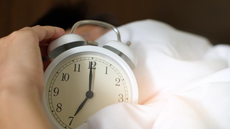 Hand reaches for an alarm clock