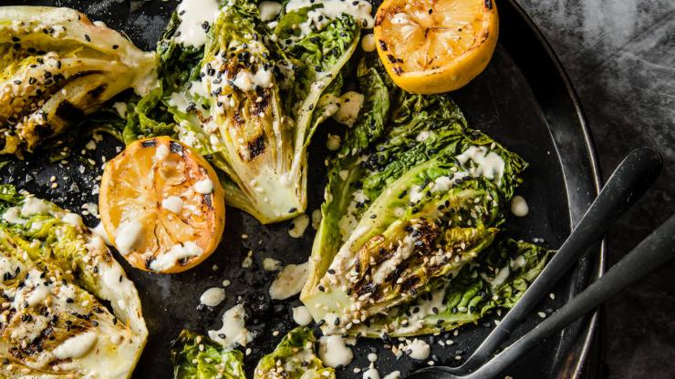 Chargrilled lettuce drizzled with lemon tahini, sesame seeds and lemons on a plate.