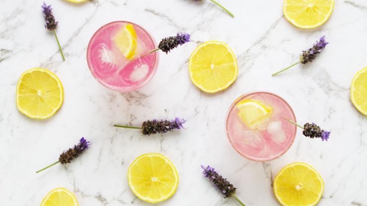 Overhead shot of lavender lemonade mocktails with lavender flowers and lemons on a table.