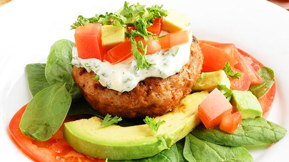 Turkey burger with avocado, tomatoes and basil.