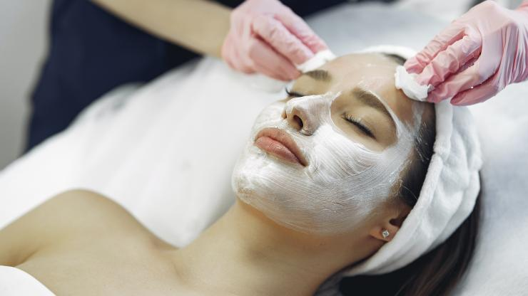 Close up of a woman getting a facial treatment as esthetician applies products to her skin.