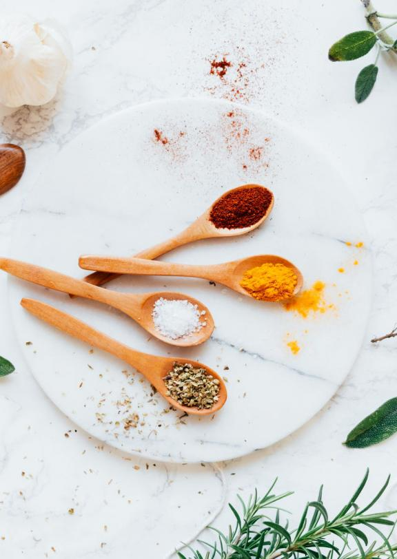 A marble table with sprigs of herbs wooden spoons holding colorful spices
