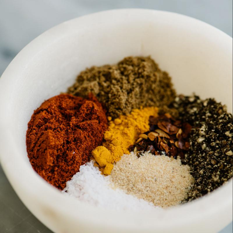 A white ceramic bowl containing colorful spices